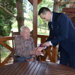 Mężczyzna w garniturze przekazuje wyróżnienie starszemu mężczyźnie.