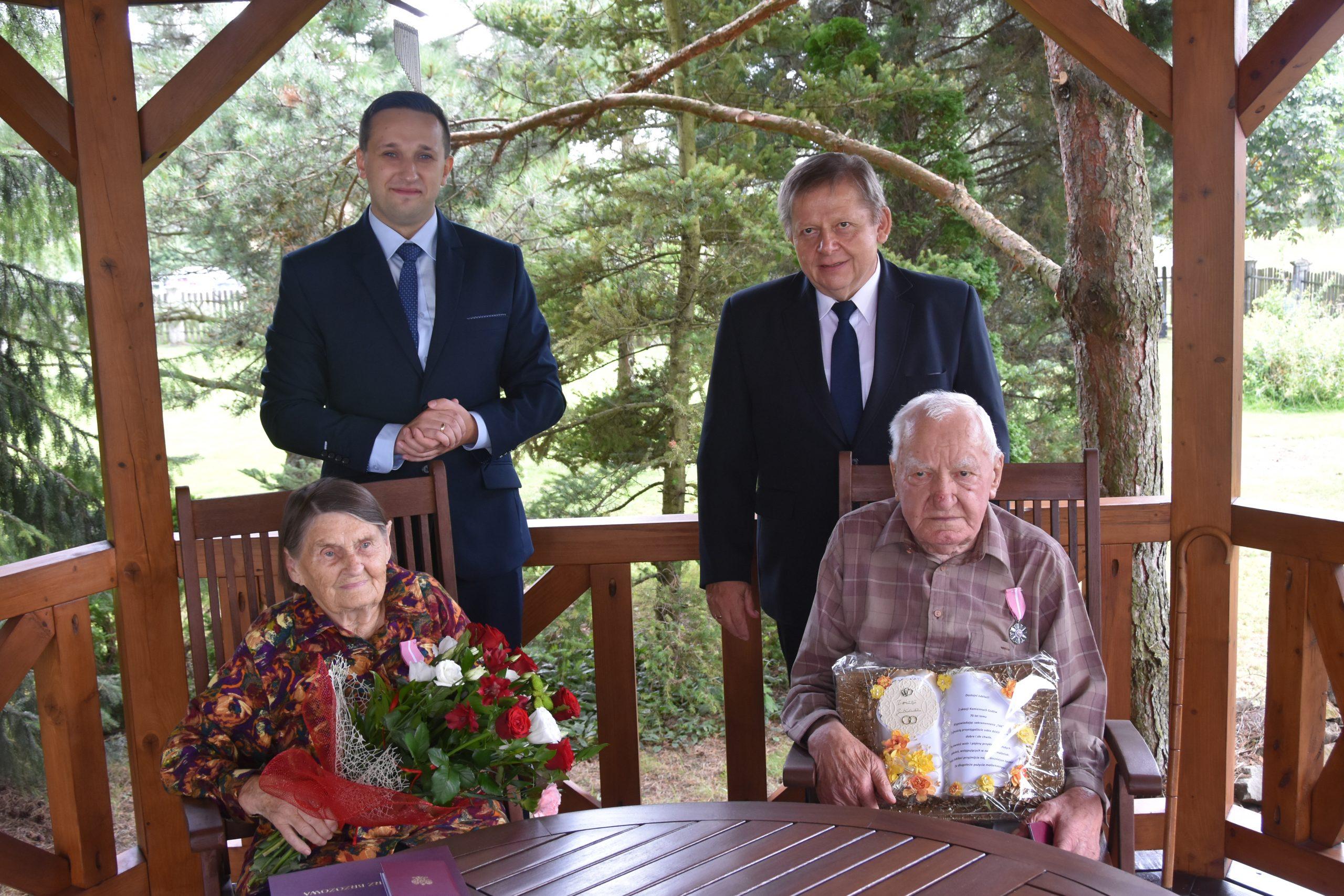 Dwóch stojacych meżczyzn w garniutrów i para staruszków siedząca przy stole.