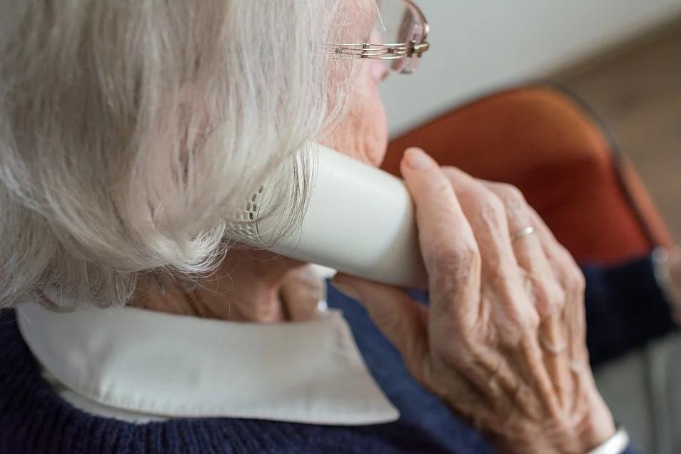 Starsza kobieta z siwymi włosami trzyma słuchawkę przy uchu . Siedzi w domu na krześle.