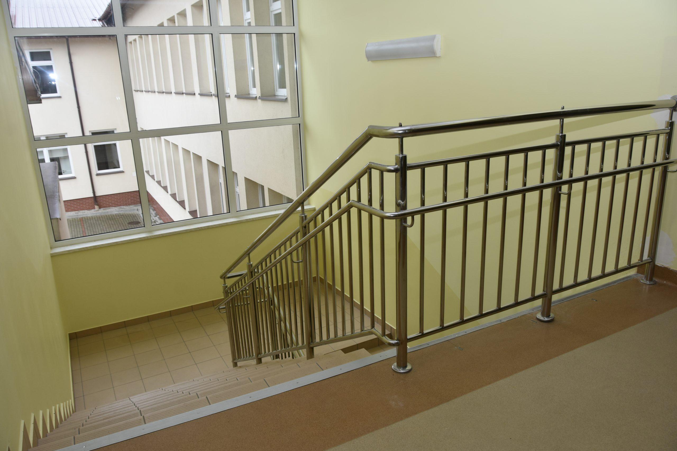 Wyremontowana klatka schodowa w szkole z nową balustradą.