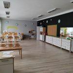 Nowo odmalowana klasa w przedszkolu koloru szarego. Po lewej stronie ustawione są stoliki po prawej szafki.