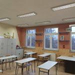 Nowo odmalowana sla lekcyjna w szkole kolotu pomarańczowego. na środku stoją stoliki i krzesełka.