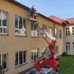 Mężczyźni na wyciągarce montują rynny przy dachu w szkole.