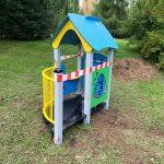 Urządzenie na placu zabaw przy przedszkolu w kształcie domku.