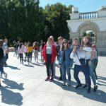 Sześcioosobowa grupa dzieci pozuje do zdjęcia na placu wyłożonym kamieniem, przed łukiem.