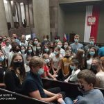 Grupa młodych ludzi siedzi w pomieszczeniu sejmu, za nimi wisi ogromna flaga z godłem Polski.