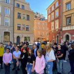 Grupa młodych ludzi podczas wycieczki stoi na placu z kostki brukowej między kamieniczkami.