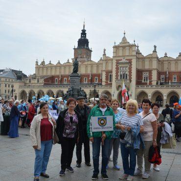 Grupa osób starszych z transparentem Gmina Brzozów, pozuje do zdjęcia na tle kamieniczek i parady w Krakowie. Za nimi panie trzymają balony, inni ubrani są w jednakowe stroje. .