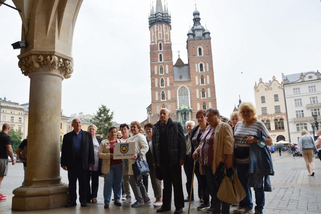 Grupa osób pozuje do zdjęcia na tle ogromengo kościoła, wyłożonego cegłami, Kobieta w centrum zdjęcia trzyma w ręce tabliczkę z napisem Gmina Brzozów.