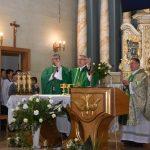 Trzech księży podczas mszy świętej w kościele stoją przed stołem głównym.