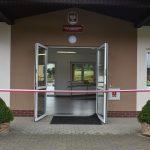 Drzwi do budynku szkoły, przed nimi wisi wstęga biało-czerwona do przecięcia.
