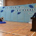 Mężczyzna w garniturze przemawia do mikrofonu przy mównicy na sali gimnastycznej.