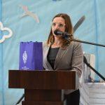 Kobieta w okularach przemawia przy mównicy do mikrofonu na sali gimnastycznej.