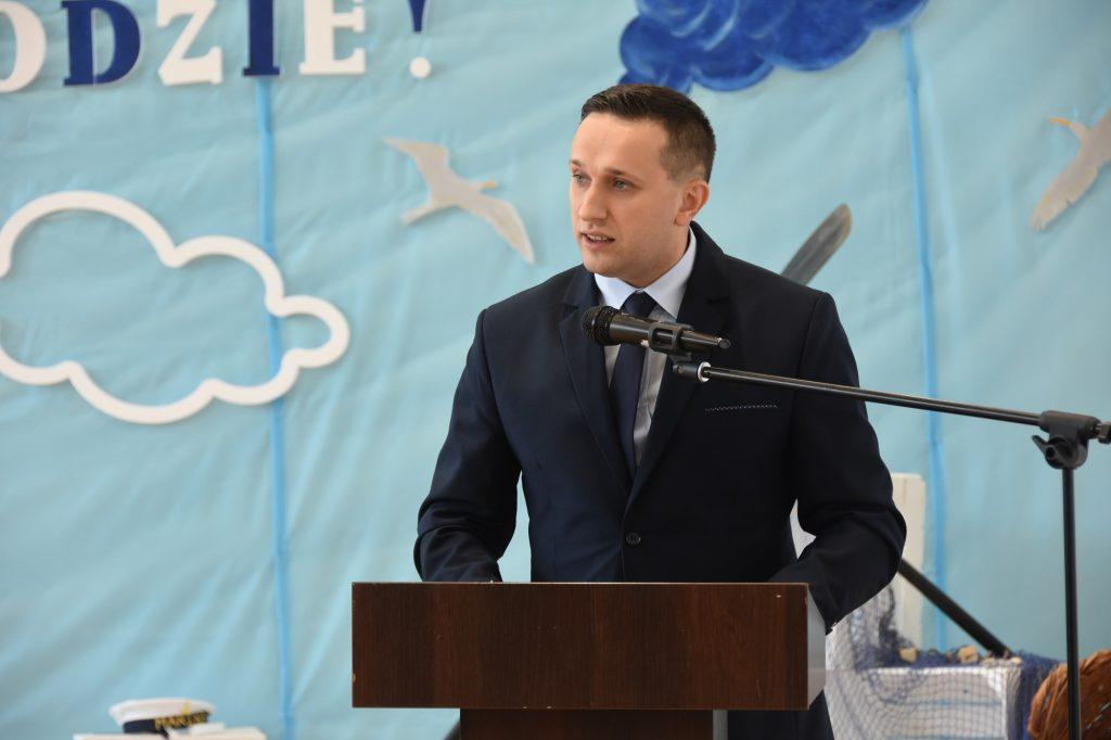 Młody mężczyzna w garniturze przemawia na sali gimnastycznej do mikrofonu przy mównicy.