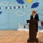 Kobieta o jasnych włosach przemawia do mikrofonu przy mównicy na sali gimnastycznej.