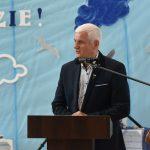 Starszy mężczyzna w siwych włosach przemawia do0 mikrofonu przy mówinicy na sli gimnastycznej.