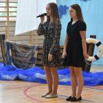 Dwie dziewczyny w sukienkach stoją przed publicznością na sali gimnastycznej. Jedna z nich trzyma mikrofon i mówi wierszyk. Za nimi dekoracja - łódka zrobiona z papieru.