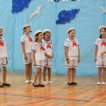 Grupa dzieci przebrana w stroje marynarskie przedstawia na sali gimnastycznej, za nimi dekoracja koloru niebieskiego.