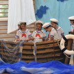 Grupa dzieci w strojach marynarskich podczas przedstawienia stoi w łodzi zrobionej z papieru.