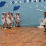 Grupa dzieci w strjach marynarskich na sali gimnastycznej występuje przed widownią.