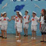 Grupa dzieci w strojach marynarskich wystepuje przed publicznością n a sali gimnastycznej.