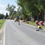 Trwają prace przy budowie chodnika przy drodze wojewódzkiej. Stoją maszyny na ulicy.