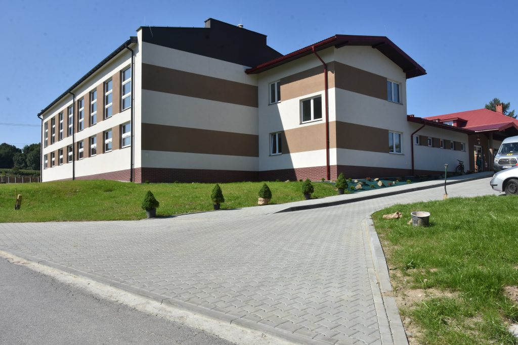 Budynek szkoły w jasnym kolorze elewacji z pasami brązowymi, obok zielony trawnik i wjazd wyłożony kostką.