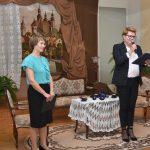 Dwie kobiety ubrane odświętnie stoją w jasnej sali i witają gości. Za nimi piękne wystrojony kącik, w którym stoją kanapa, krzesła i stolik z haftowanym obrusem.