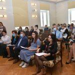 Grupa osób siedzi w maseczkach na jasnej sali konferencyjnej, oglądają przedstawienie.