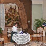 Dwie kobiety rozgrywają scenę w jasnej sali i specjalnie do tego przygotowanym kąciku. Jedna z nich stoi druga z kolei siedzi na kanapie.