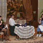 Trzy kobiety siedzą w jasnej sali i rozgrywają sceny. Dwie młodsze siedzą na krzesłach, starsza siedzi na kanapie.