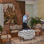 Młody mężczyzna i kobieta rozgrywają scenę w jasnej sali, w której stoją foetel i kanpa oraz stolik z haftowanym obrusem.
