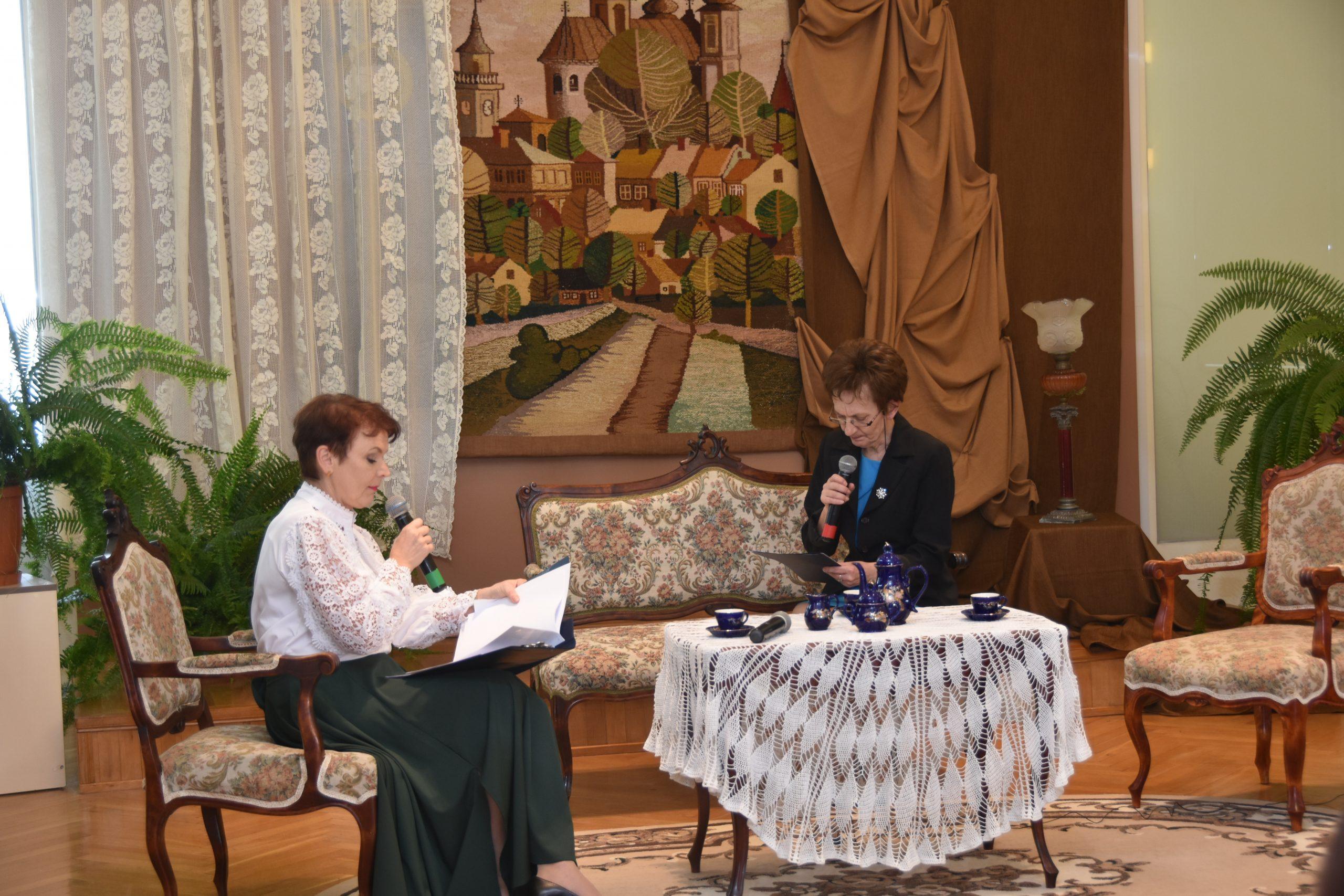 Dwie kobiety siedzą przy stoliku, na którym leży haftowana serwetka. Panie czytają swoje role do mikrofonu. Za nimi piękna sceneria w kolorach brązowych.