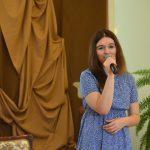 Młoda dziewczyna w niebieskiej sukience i ciemnych włosach śpiewa piosenkę.