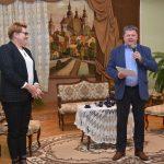 Kobieta i mężczyzna w garniturze przemawiają do mikrofonu, w jasnej sali w której stoi kanapa, fotele i stolik z haftowanym obrusem.