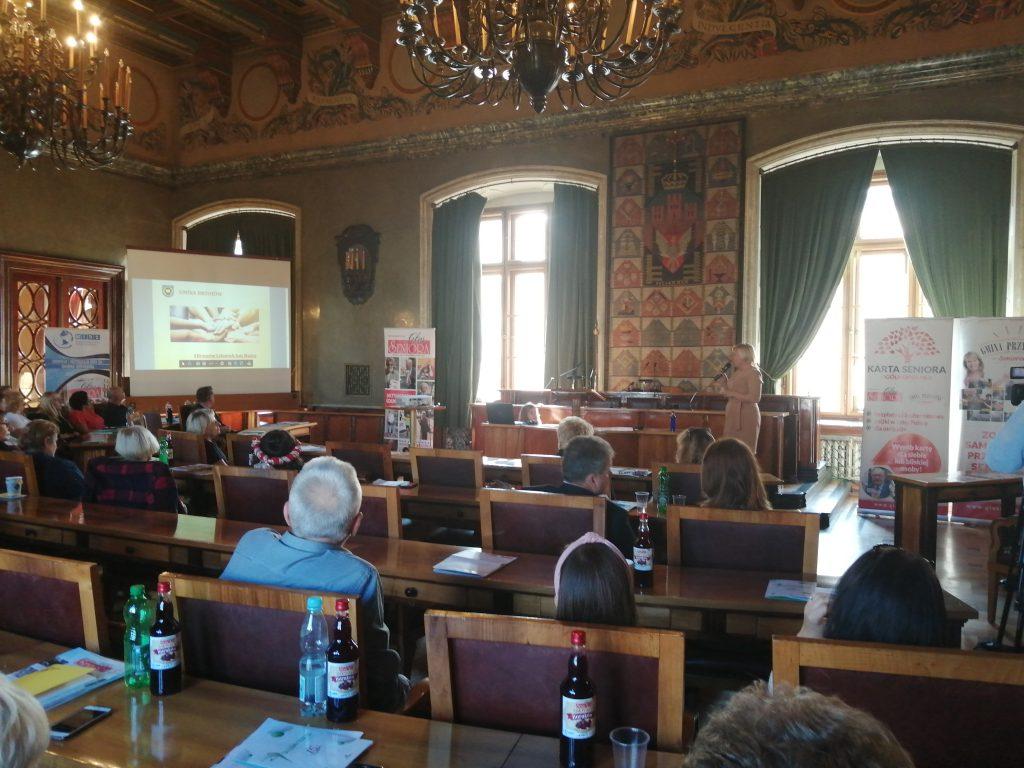 Grupa osób siedzi na dużej sali i przysłuchują się wypowiedziom kobiety, która posługuje się prezentacją multimedialną.
