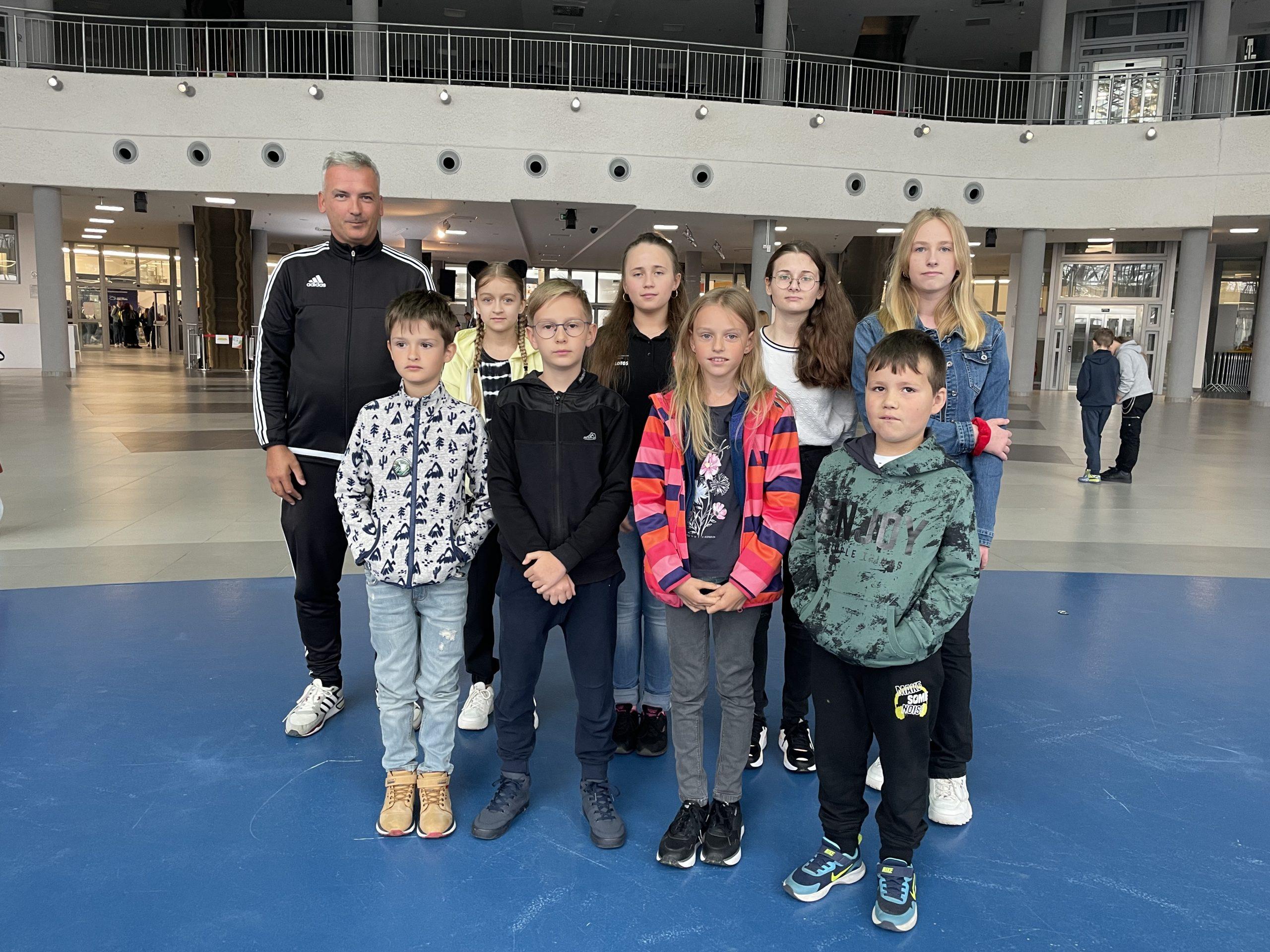 Grupa dzieci stoi w dużym pomieszczeniu konferencyjnym.