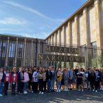 Kilkudziesięciu osobowa grupa młodych ludzi pozuje do zdjęcia podczas wycieczki na tle bramy do jasnego budynku muzeum.