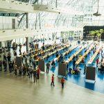Duża jasna sala konferencyjna , na środku hali stoją stoły, a na nich rozstawione szachy. Na sali przebywa kilkaset osób.