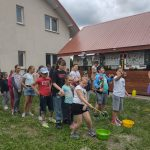 Grupa dzieci na zewnątrz gra w gry zespołowe.