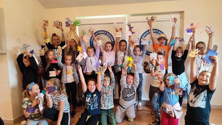 Grupa dzieci pozuje do zdjęcia w jasnej sali z rękoma uniesionymi do góry i machającymi.