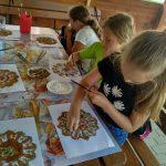 Dziewczynki siedzą przy stoliku i malują obrazki.