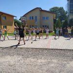 Grupa dzieci na świeżym powietrzu tańczy na placu wyłożonym kostką.