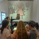 Grupa dzieci ogląda przez projektor bajkę.