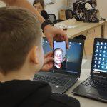 Chłopiec w czarnej bluzie przegląda się w telefonie. Siedzi w sali lekcyjnej.