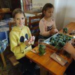 Dwie dziewczynki siedzą przy stoliku i uczą się marynować ogórki.