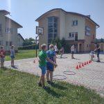 Grupa dzieci na świeżym powietrzu gra w gry zespołowe.