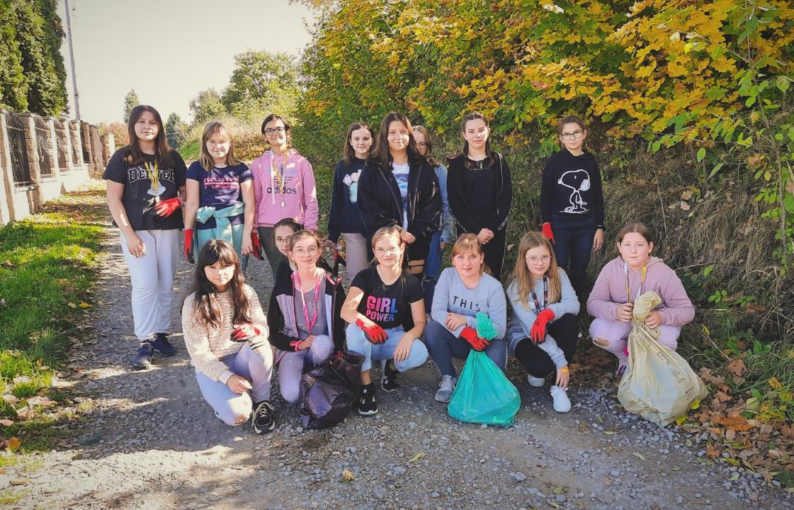 grupa dziewczynek ze szkoły podstawowej w Starej Wsi ubrana w kurtki oraz wyposażona w rękawice i worki na śmieci, gotowa do sprzątania świata, na tle chaszczy.